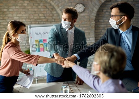 Happy business team wearing protective face masks while colliding their fists on a meeting in the office.  Royalty-Free Stock Photo #1762602305