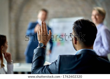 Rear view of a businessman raising his hand to ask the question during business presentation in the office. Royalty-Free Stock Photo #1762602320