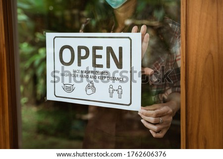 wear masks, keep your distance and wash hand sign on shop front door when new normal during coronavirus outbreak in the city open her shop for business