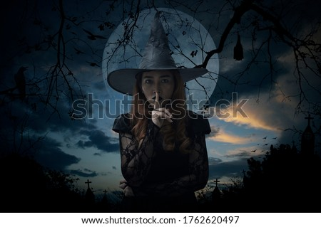 Halloween witch showing silence sign with finger standing over cross, church, crow, bat, birds, dead tree, full moon and sunset sky, Halloween mystery concept Royalty-Free Stock Photo #1762620497