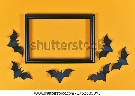 Seasonal Halloween flat lay with black flying paper craft bats around empty picture frame on orange background
