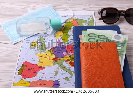 a printed color map of europe and the means of individual protection as the traveling during coronovirus pandemic period concept