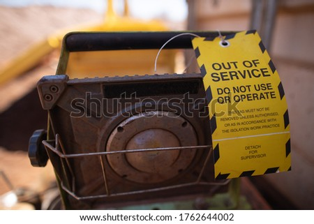 Safety workplaces yellow out of service tag attached on faulty damage defect of light at construction site Perth, Australia