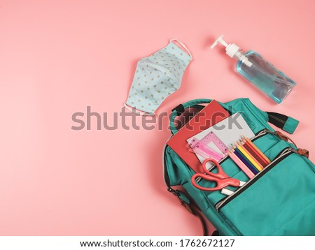 COVID-19 prevention while going back  to school  and new normal  concept.Top view of backpack with school supplies , blue polka dot fabric masks and sanitizer gel on pink background. #1762672127