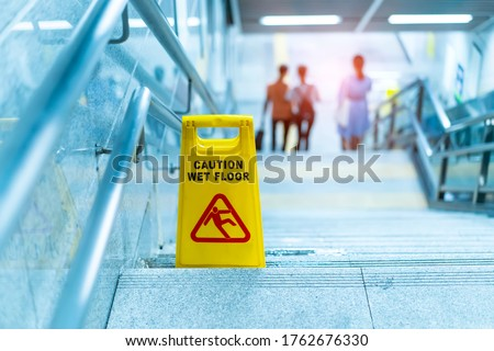 """""""Caution wet floor"""" sign in stairs Royalty-Free Stock Photo #1762676330"""