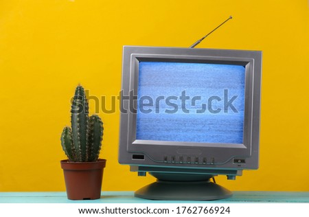 Mini Retro tv antenna receiver on yellow background. Old fashioned TV set with cactus. Television noise, no signal. 80s Royalty-Free Stock Photo #1762766924