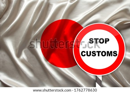 customs sign, stop, attention on the background of the silk national flag of japan, the concept of border and customs control, violation of the state border, tourism restrictions