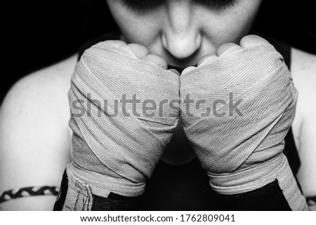Muay Thai fighter girl preparing for battle. Closeup black and white portrait against black background. Royalty-Free Stock Photo #1762809041