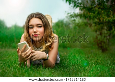 beautiful girl lies on green grass with a smartphone in her hands in the park Royalty-Free Stock Photo #1762814183