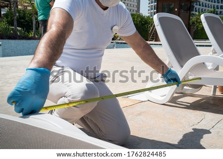 Coronavirus safety distance. Covid-19 social distance measurement between deck chairs by the pool Royalty-Free Stock Photo #1762824485