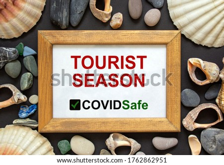 Wooden picture frame with inscription 'tourist season covidsafe' on beautiful black background. Sea stones and seashells. Concept.