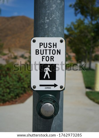 Crosswalk button and sign on street pole.