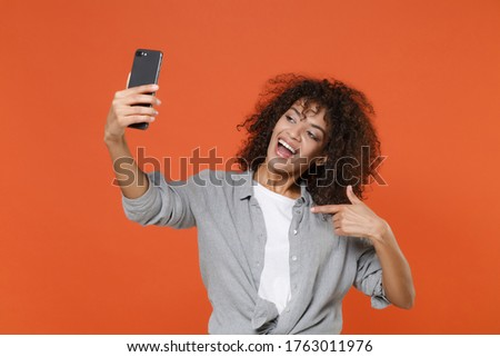 Excited young african american woman in casual clothes isolated on orange background. People lifestyle concept. Mock up copy space. Doing selfie shot on mobile phone, pointing index finger on herself