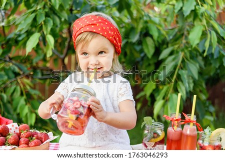 Lemonade Stand. Adorable little girl trying to sell lemonade. strawberry lemonade with ice and mint as summer refreshing drink in jars. Cold soft drinks with fruit. Child drinking lemonade in jar #1763046293