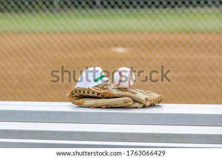 Baseball glove, ball and N95 respirator mask at baseball field. Concept of reopening America sporting and recreational events during Covid-19 coronavirus pandemic during lockdown closure. New normal #1763066429