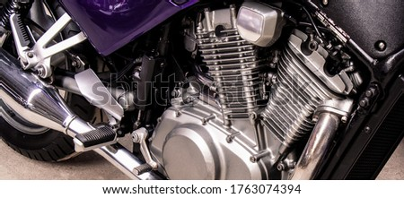 Silver v-twin shaped engine of sports motorcycle close-up. Pistons, cylinders, pedals, gearbox, back wheel motorbike. Chrome motor parts. Repair, bike maintenance in the garage. Banner for web site