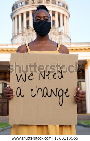 Serious young african american woman wear black face mask stand outdoors hold sign protesting alone on street. Black female peaceful protest against racism for rights, racial equality, justice concept