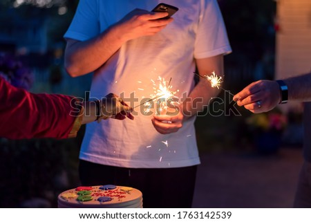 Young man snapping a picture of sparklers and cake at a backyard birthday celebration