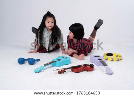 Two little girls laying down on ground floor.Beside ukulele,violin,Maracas and Tambourine,doing activity together #1763184650