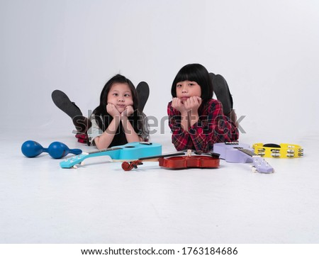Two little girls laying down on ground floor.Beside ukulele,violin,Maracas and Tambourine,doing activity together.making cheeky face,for funny #1763184686