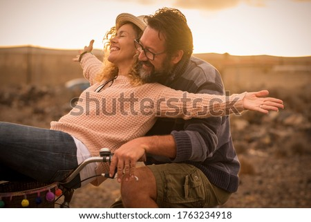 Happy adult people cheerful couple enjoy the outdoor leisure activity riding a bike together man carrying woman and laugh a lot in friendship and relationship - active youthful persons #1763234918