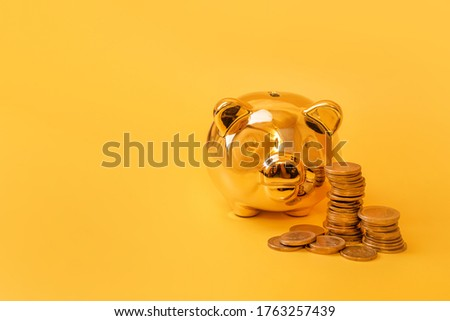 Golden piggy bank with money towers on yellow background. Stack of euro coins near golden money box. Money pig, money saving, moneybox, finance and investments concept. Free space for text