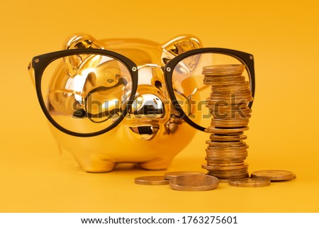 Golden piggy bank wearing glasses with money towers. Stack of euro coins near golden money box. Money pig, money saving, moneybox, pile of coins. Finance and investments. Free space for text