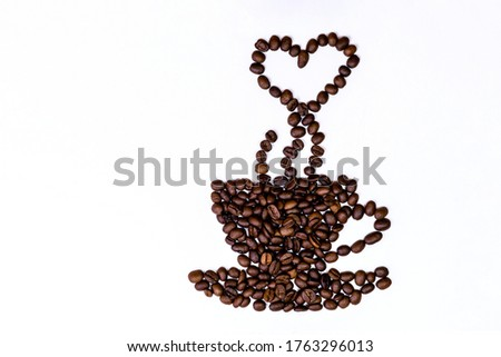 Close up picture of cup of coffee with the heart shaped steam in a  made of roasted beans on the white blackground.