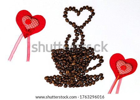 Close up picture of cup of coffee with the heart shaped steam in a  made of roasted beans and read hearts around on the white blackground.
