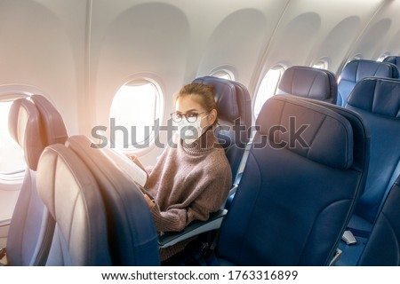 A young woman wearing face mask is traveling on airplane , New normal travel after covid-19 pandemic concept  #1763316899