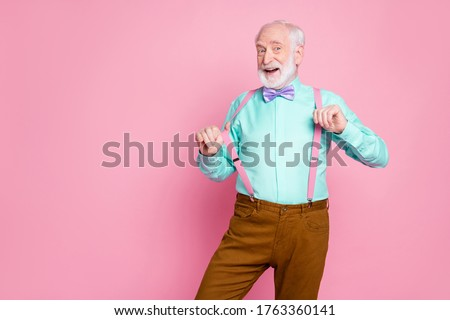 Photo of funny stylish grandpa positive emotions before senior party meeting touch hold fingers suspenders wear shirt violet bow tie brown pants isolated pink pastel color background #1763360141