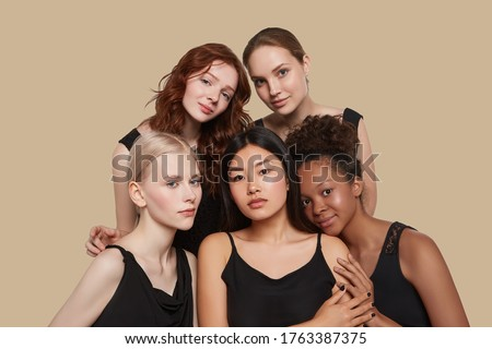 The real beauty exists in every corner of the world and is presented by women of all races. Group portrait of five beautiful ladies in black tops and with different skin and hair colour. #1763387375