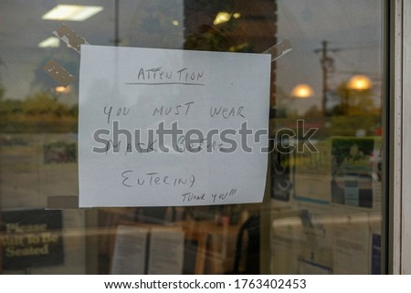 Written sign in the window of a store saying that you mist wear a mask before entering