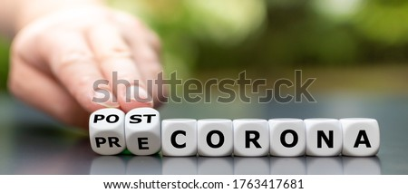 Symbol for the end of the corona pandemic. Hand turns dice and changes the expression pre-corona to post- corona. Royalty-Free Stock Photo #1763417681