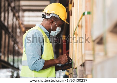 Black African worker wear protective face mask and helmet check stock in warehouse. Concept of new normal work in industry, factory after Covid 19 pandemic #1763430239