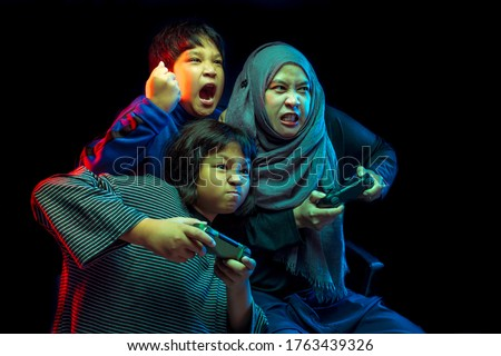 The picture of a happy Muslim family consisting of a mother and son and daughter playing a game console with a face that is very entertaining.