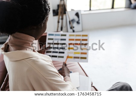 Back view photo of young african woman interior designer sitting on sofa indoors at home while holding catalogue of colors