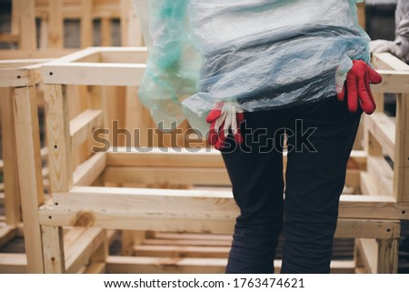 Girl works with wood on construction site. View from back, she has gloves in back pockets. #1763474621