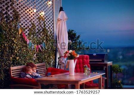 cute siblings having fun, watching cartoons on the phone, spending time on cozy rooftop patio in summer evening