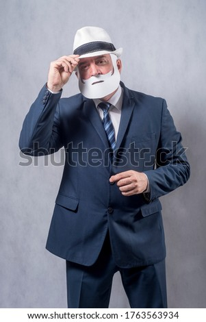 A grey-haired dignified man in a blue suit and a tie in the role of a successful businessman who is playing while wearing a face mask of a beard and a mustache against a grey background. #1763563934