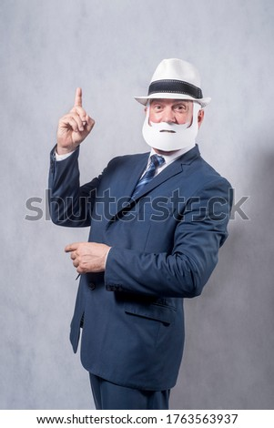 A grey-haired dignified man in a blue suit and a tie in the role of a successful businessman who is playing while wearing a face mask of a beard and a mustache against a grey background. #1763563937