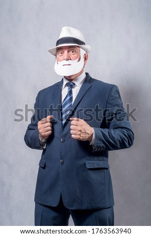 A grey-haired dignified man in a blue suit and a tie in the role of a successful businessman who is playing while wearing a face mask of a beard and a mustache against a grey background. #1763563940