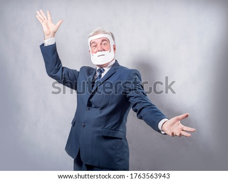 A grey-haired dignified man in a blue suit and a tie in the role of a successful businessman who is playing while wearing a face mask of a beard and a mustache against a grey background.. #1763563943