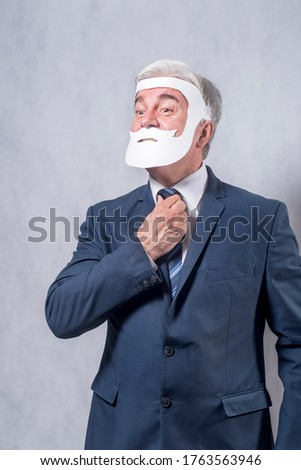 A grey-haired dignified man in a blue suit and a tie in the role of a successful businessman who is playing while wearing a face mask of a beard and a mustache against a grey background.. #1763563946