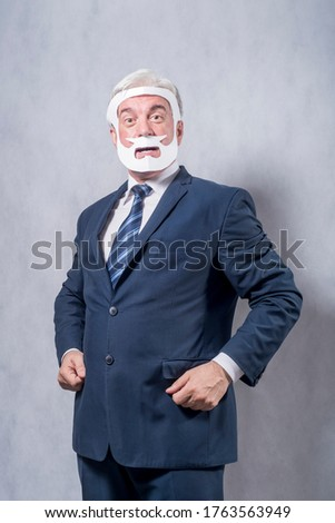 A grey-haired dignified man in a blue suit and a tie in the role of a successful businessman who is playing while wearing a face mask of a beard and a mustache against a grey background.. #1763563949