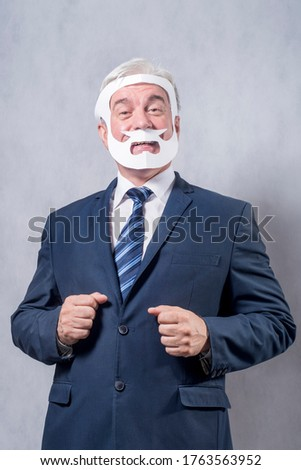 A grey-haired dignified man in a blue suit and a tie in the role of a successful businessman who is playing while wearing a face mask of a beard and a mustache against a grey background.. #1763563952