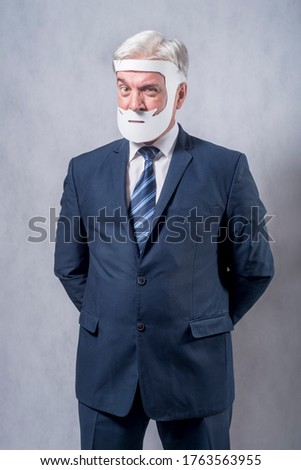 A grey-haired dignified man in a blue suit and a tie in the role of a successful businessman who is playing while wearing a face mask of a beard and a mustache against a grey background.. #1763563955