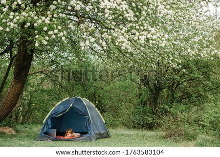 Children tourism. Child using laptop in the tent at the campsite. Girl watching cartoon on gadget. Kid girl in a campaign in a tent. Family summer vacation in nature.
