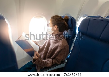 A young woman wearing face mask is traveling on airplane , New normal travel after covid-19 pandemic concept  #1763637644