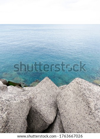 Breakwater. Rocks by the blue sea merge with the horizon. Close-up of a rock-armor breakwater. Calm sea landscape. #1763667026